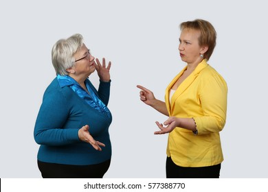 Old mother blames adult daughter on gray background - senior and middle age women