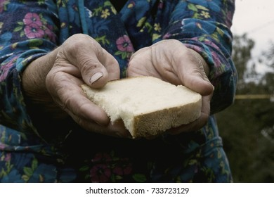 An old mother holds a piece of bread in her hands