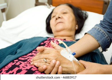 old mother sick in hospital. hand being hold by her caring daughter
