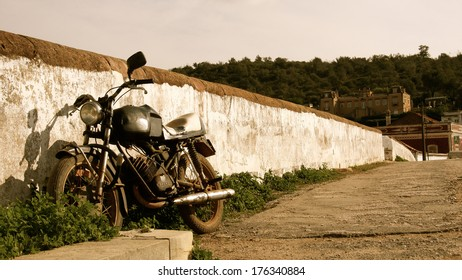 An old motor cycle parked against a fench