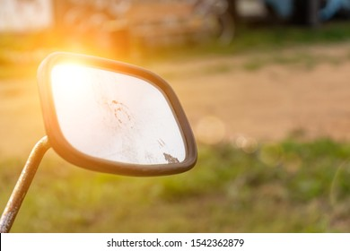 Old motorcycle rearview mirror with a sun reflection close up on countryside green background.