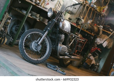 Old motorcycle, which needs to be repaired, in the workshop, with set of tools