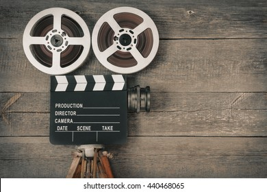 Old movie camera, consisting of a tripod, lens, film reels and clapperboards