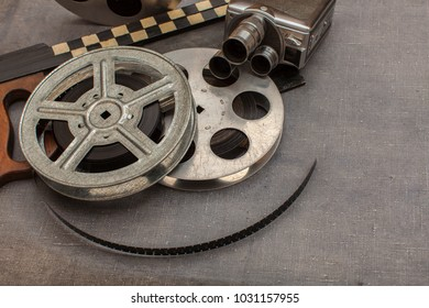 Old movie camera, film reels and clapperboards on the painted background