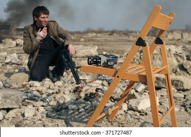 Old movie camera lying on a wooden chair on the background of the set area with an actor.