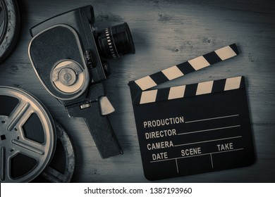 An old movie camera, movie reels and a clapperboard lie on a wooden board. View from above