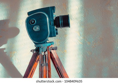 An old movie camera stands on a wooden tripod against a concrete wall in the studio