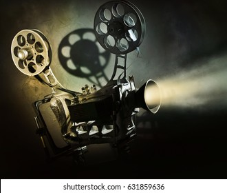 Old movie projector with the film on the dark background