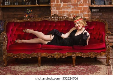 Old movies style: elegant young woman lying on a sofa.