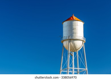 An old multi-column elevated water tower and water tank stands against a solid blue sky in a small town.