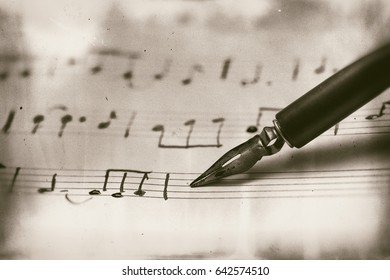Old musical score with fountain pen Ruined vintage style photograph