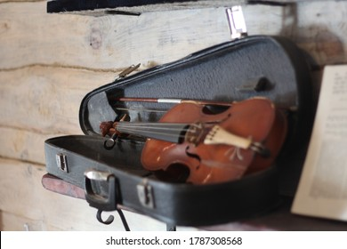 Old musician instrument violin with a bow in a case on a wooden shelf.