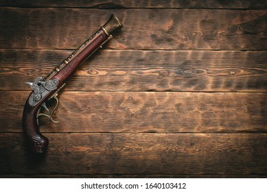 Old musket gun on pirate desk table concept background with copy space.