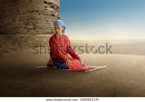 Old muslim man kneeling and praying on the outdoor