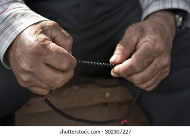 Old muslim Man with rosary praying
