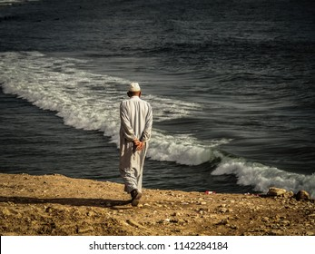 old muslim man walking to the beach in morocco