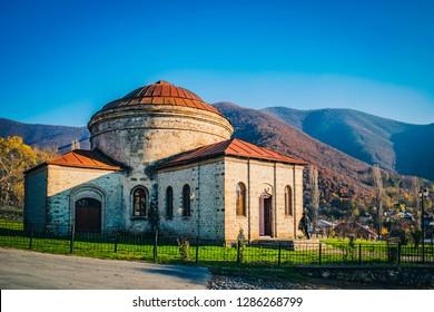 Old Muslim temple and mountains on a sunny autumn day. 2018, Sheki, Azerbaijan.