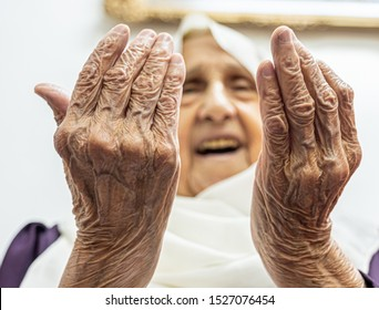 Old muslim woman praying for god to bless her and give her strength