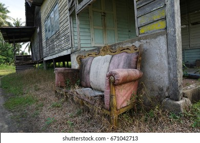 Old n torn out sofa outside the abandoned house