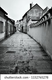 Old narrow and picturesque street in winter morning with footprints. Street is in town Trebon, Czech republic, South Bohemia. Black and white image.
