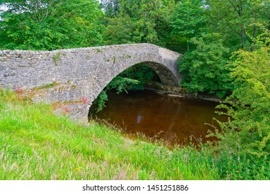 An old narrow stone bridge, almost overgrown by trees, crosses the River Ribble near Stainforth, Yorkshire