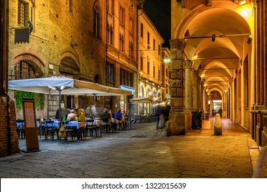 Old narrow street with arcade in Bologna, Emilia Romagna, Italy. Night cityscape of Bologna.