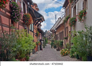 Old narrow street with a lot of flowers on the windows, Europe