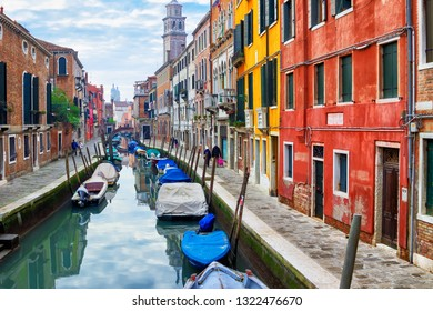 Old narrow water canal with boats in Venice, Italy. Street with colorful architecture of Venice. Venetian cityscape.