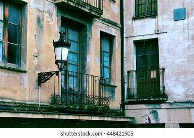 Old neglected house wall with balcony and lamp. Berga, Catalonia, Spain