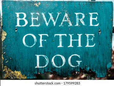 Old and neglected wooden beware of the dog sign.