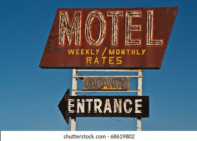 Old neon motel sign advertising monthly and weekly rates also shows if there is a vacancy and where the entrance is