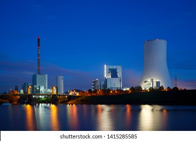An old and a new coal power station side by side with reflection in the water and night blue sky.