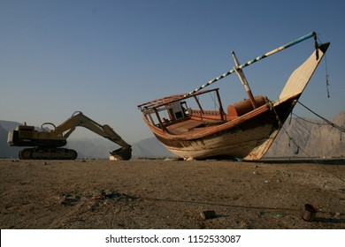 Old and new juxtaposition of machine and traditional dhow, Khasab, Oman