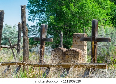 Old New Mexico Graveyard with Wood Crosses and Headstones,  an old Ladder and Barbed Wire Fence, Tall Grass and Trees.