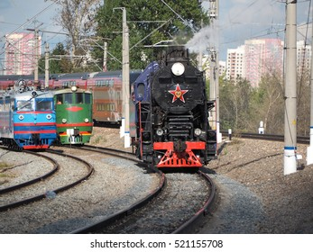old and new: Russian steam train rides on the background of modern locomotives