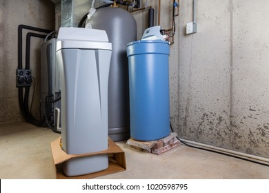 Old and new water softener tanks in a utility room waiting for replacement to remove minerals from hard water