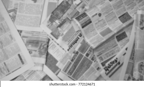 Old newspapers scattered on the floor. Lots of retro journals with headlines, articles and photos. Background texture, blurred, top view