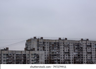 old nine-story building. A multi-storey residential building of the Soviet period. Gray faceless windows and walls. Russia.