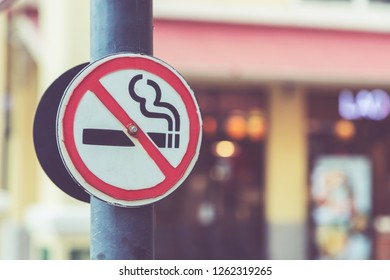 Old No Smoking Label Stick to the pole in the public park with blur background