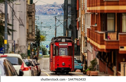 Old nostalgic tram going through the streets of Kadikoy on the Asian side of Istanbul. The trendy neighborhood is full of colorfull buildings. And Marmara Sea - Shutterstock ID 1447963433