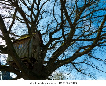 old nostalgic weathered wooden treehouse high up in a winter tree