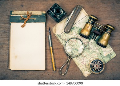 Old notebook, compass, map, vintage binoculars, pen and inkwell, pocket knife, magnifying glass on wooden background
