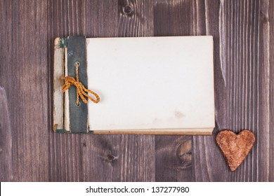 Old notebook and heart on wood background