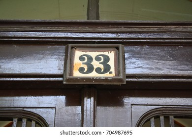 Old number 33 sign, thirty-three written over an entrance door of a building.