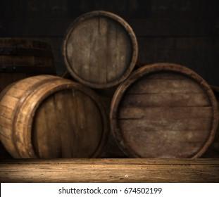 Old oak barrel on a wooden table. Behind blurred dark background.