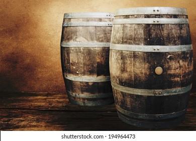 Old oak barrels on the wall background.