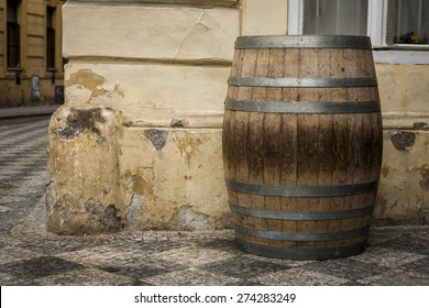 The old oak wine barrel, metal rims with rust, barrel standing on the street.