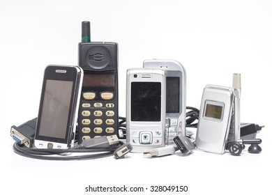 Old and obsolete mobile phone and accessory on white