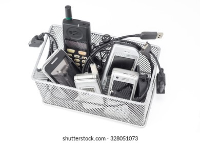 Old and obsolete mobile phone and accessory in basket on white