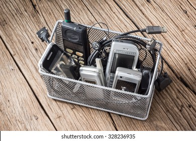 Old and obsolete mobile phone and accessory in basket on old wood